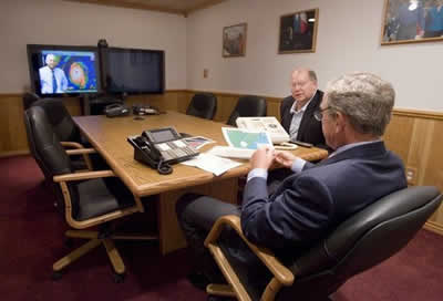 President George W. Bush is handed a map by Deputy Chief of Staff Joe Hagin, center, during a video teleconference with federal and state emergency management organizations on Hurricane Katrina from his Crawford, Texas ranch on Sunday August 28, 2005.